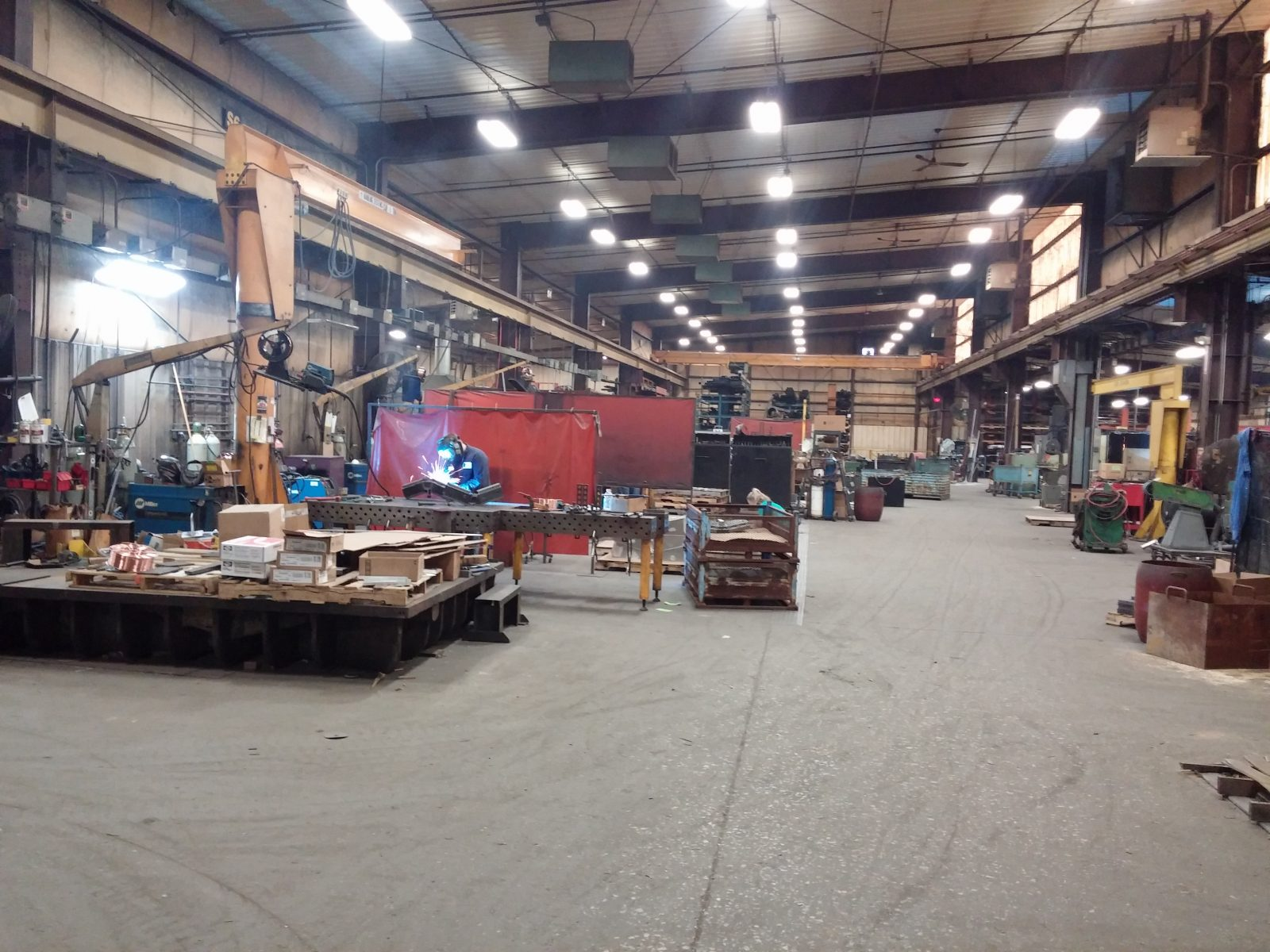 Main fabrication warehouse with worker welding